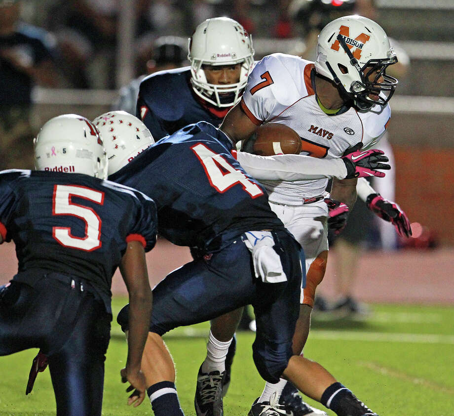 Marquis Warford twists away from Rough Rider tacklers in the first half as Madison plays Roosevelt at Heroes Stadium on October 5, 2012. Photo: Tom Reel, Express-News / ©2012 San Antono Express-News