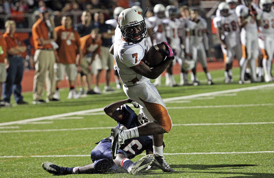 Maverick running back Marquis Warford spins away from Frank Barnes on a touchdown run in the second quarter as Madison plays Roosevelt at Heroes Stadium on October 5, 2012. Photo: Tom Reel, Express-News / ©2012 San Antono Express-News