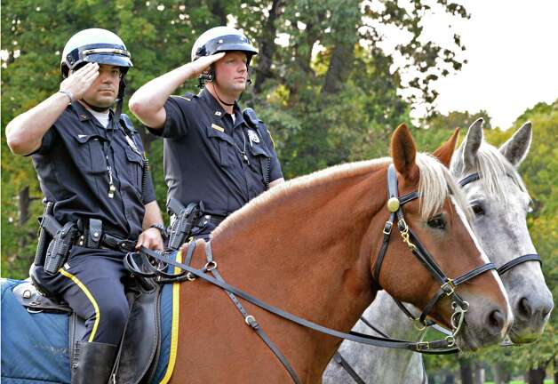 "Albany mounted police officers David Basile, left, and John Dwyer aboard ""Austin"" and ""Mighty Joe"" respectively, salute during the the 100th anniversary rededication of the Soldiers and Sailors Monument in Albany's Washington Park Friday Oct. 5, 2012. (John Carl D'Annibale / Times Union) Photo: John Carl D'Annibale / 00019555A"