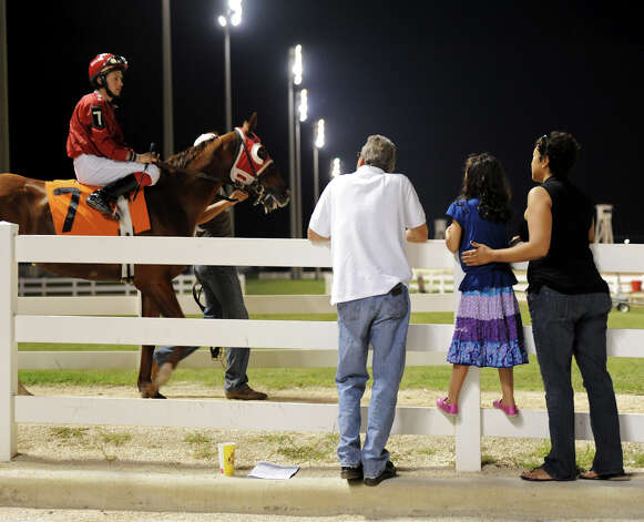 A family watches as  	Special Blushing (7) walks to the track before the start of the fourth race during Retama Park's opening night of the 2012 thoroughbred horse racing season in Selma, Friday, October 5, 2012.