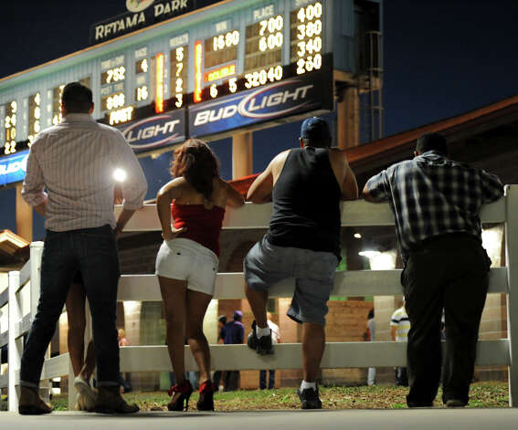 A group of people watch as horses wait in their stalls in the paddock before the fourth race during Retama Park's opening night of the 2012 thoroughbred horse racing season in Selma, Friday, October 5, 2012.