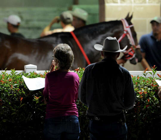 A couple watches horses walk by in the paddock before the fourth race during Retama Park's opening night of the 2012 thoroughbred horse racing season in Selma, Friday, October 5, 2012.