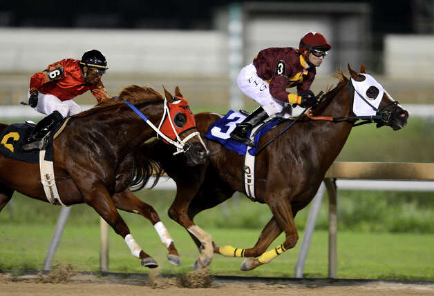 Money Seeker (3) edges past Big Rojo (6) in the third race during Retama Park's opening night of the 2012 thoroughbred horse racing season in Selma, Friday, October 5, 2012.