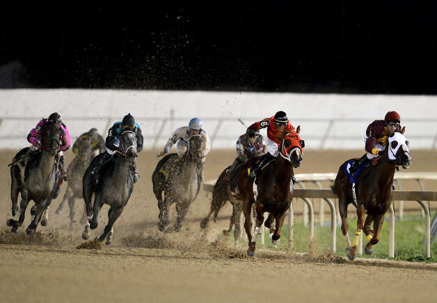 Horses hit the top of the home stretch in the third race during Retama Park's opening night of the 2012 thoroughbred horse racing season in Selma, Friday, October 5, 2012.