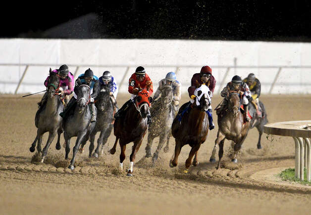 Horses come around the final turn in the third race during Retama Park's opening night of the 2012 thoroughbred horse racing season in Selma, Friday, October 5, 2012.