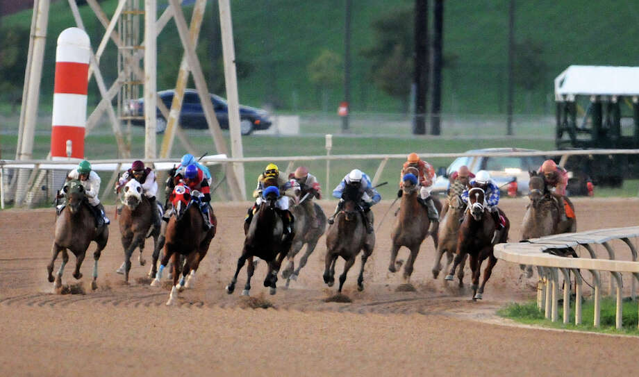Horses come around the final turn in the second race during Retama Park's opening night of the 2012 thoroughbred horse racing season in Selma, Friday, October 5, 2012.