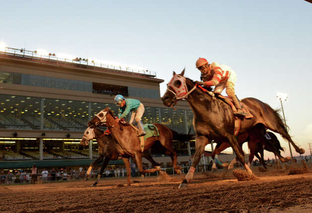 A group of horses cross the finish line during Retama Park's opening night of the 2012 thoroughbred horse racing season in Selma, Friday, October 5, 2012.