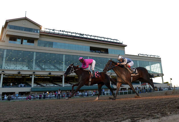 Dulce Fina (8) and  	Dancin' Dixie Card (2) cross the finish line  during the first race of Retama Park's opening night of the 2012 thoroughbred horse racing season in Selma, Friday, October 5, 2012.