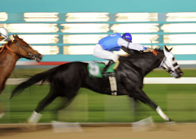 Risen in Deed (5) is just a blur as it races past to win the fourth race during Retama Park's opening night of the 2012 thoroughbred horse racing season in Selma, Friday, October 5, 2012.