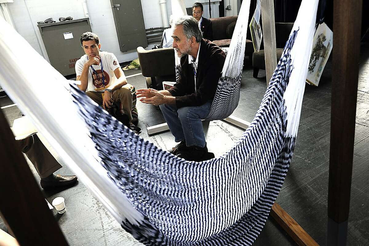 Dan Salcedo(R) CEO of OpenEntry.com sits in a sustainable hammock made by Joe Demin's(L) company Yellow Leaf, while discussing online social responsibility with other attendees. SOCAP 2012, the annual Social Capital Markets Conference, was held at Fort Mason in San Francisco, CA Wednesday October 3rd, 2012.