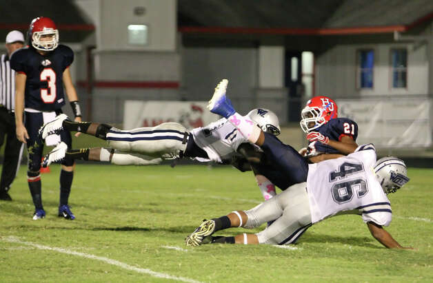 Hardin-Jefferson running back Peyton Gloston, No. 21, is tackled by Colin Janice, No. 21, and Jhayllien Monette, No. 46, during the game Friday against West Orange-Stark in Sour Lake. Matt Billiot Photo: Matt Billiot