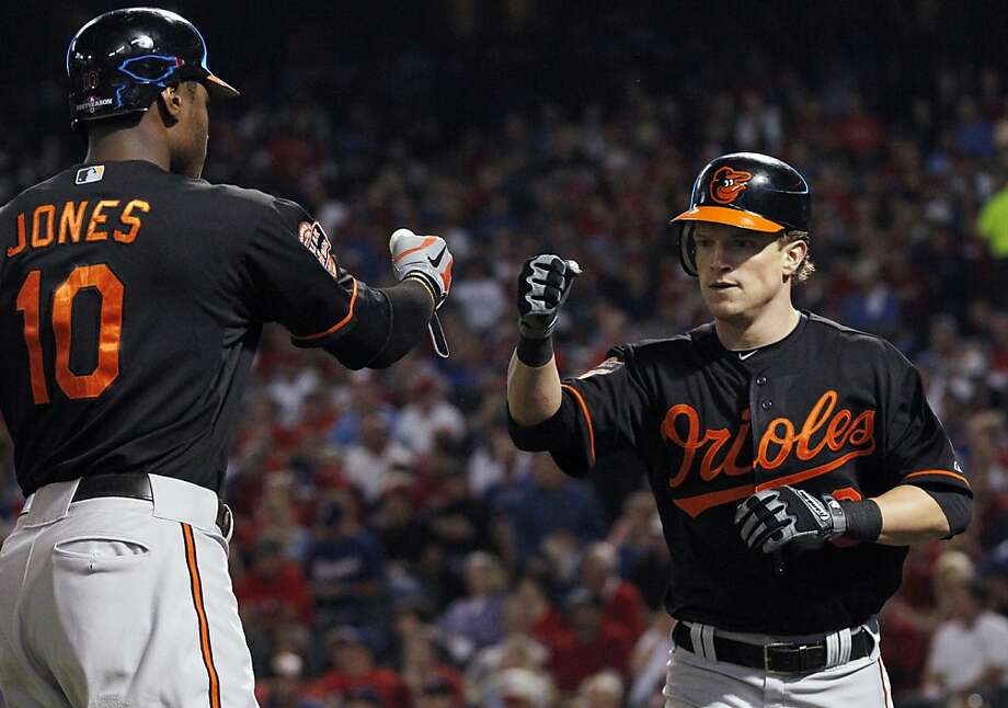 Nate McLouth (right) is congratulated by Adam Jones after scoring the Orioles' first run on a single by J.J. Hardy in the first inning. Photo: LM Otero, Associated Press