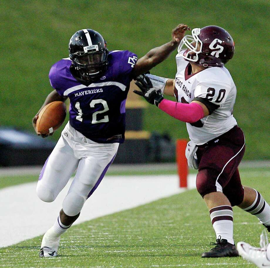 Morton Ranch quarterback Quandre Washington #12 gives Cinco Ranch's Taylor Holt #20 a stiff arm during a high school football game between Morton Ranch and Cinco Ranch at Rhodes Stadium October 5, 2012 in Katy, Texas. Photo: Bob Levey, Houston Chronicle / ©2012 Bob Levey