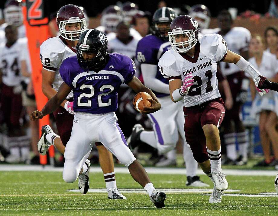 Morton Ranch running back E.J. Achelus #22  looks for room to run as Cinco Ranch's Cameron Moore #21 pursues during a high school football game between Morton Ranch and Cinco Ranch at Rhodes Stadium October 5, 2012 in Katy, Texas. Photo: Bob Levey, Houston Chronicle / ©2012 Bob Levey