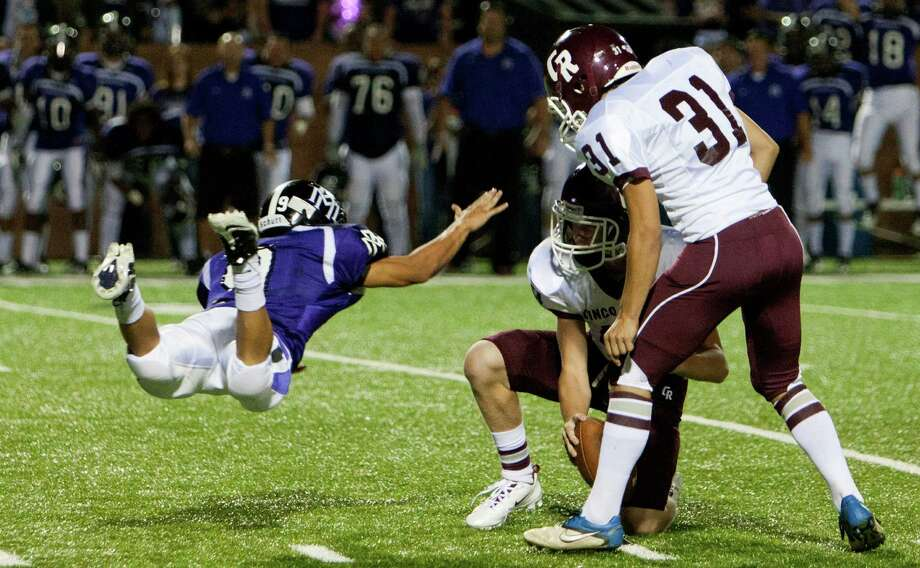 Cinco Ranch holder Geryn Young #13 can't handle the snap cleanly for kicker Jared Barrera #31 in the extra period as Morton Ranch's Christian Escobar #9 attempts to block during a high school football game between Morton Ranch and Cinco Ranch at Rhodes Stadium October 5, 2012 in Katy, Texas. Morton Ranch won 38-35. Photo: Bob Levey, Houston Chronicle / ©2012 Bob Levey