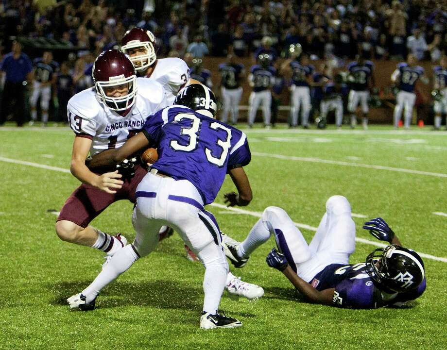 Cinco Ranch's Geryn Young #13 is tackled by Morton Ranch's Na Voine Gurley #3 in the extra period as Young mishandled the snap on the field goal attempt during a high school football game between Morton Ranch and Cinco Ranch at Rhodes Stadium October 5, 2012 in Katy, Texas. Photo: Bob Levey, Houston Chronicle / ©2012 Bob Levey