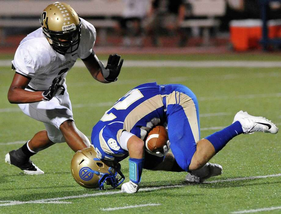 Seguin's Colton Applewhite, left, closes in on Alamo Heights' Christian Biedenharn during a high school football game, Friday, Oct. 5, 2012, at Alamo Heights High School in San Antonio. Photo: Darren Abate, Express-News