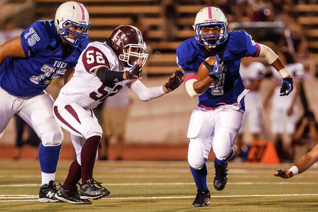 Lanier running back Matthew Carson (right) finds room to run around Highlands' Adre Servin as Kristian Aguirre comes in to block during the first quarter of their game at Alamo Stadium on Oct. 5, 2012.  Lanier won the game 28-24.  MARVIN PFEIFFER/ mpfeiffer@express-news.net Photo: MARVIN PFEIFFER, Express-News / Express-News 2012