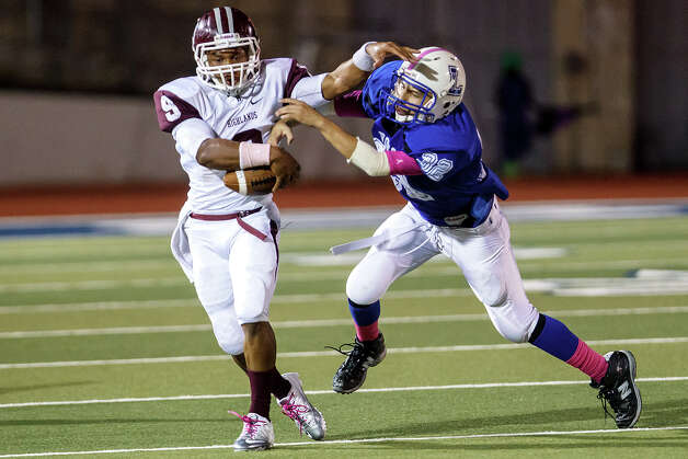 Highlands running back Jacolby Bass (left) tries to shed a tackle by Lanier's Carlos Gutierrez during the second quarter of their game at Alamo Stadium on Oct. 5, 2012. Lanier won the game 28-24.   MARVIN PFEIFFER/ mpfeiffer@express-news.net Photo: MARVIN PFEIFFER, Express-News / Express-News 2012