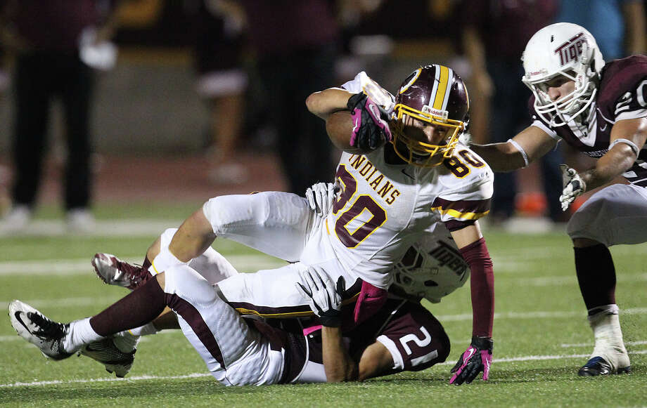Harlandale's Nathan Ibarra (80) gets brought down by Floresville's Dadrian Contreras (21) and John Huber (20) in high school football in Floresville, Texas on Friday, Oct. 5, 2012. Photo: Kin Man Hui, Express-News / ©2012 San Antonio Express-News