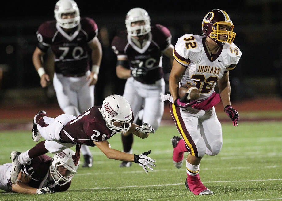 Harlandale's Jonathan Rodriguez (32) pulls away from Floresville's Dadrian Contreras (21) in high school football in Floresville, Texas on Friday, Oct. 5, 2012. Photo: Kin Man Hui, Express-News / ©2012 San Antonio Express-News