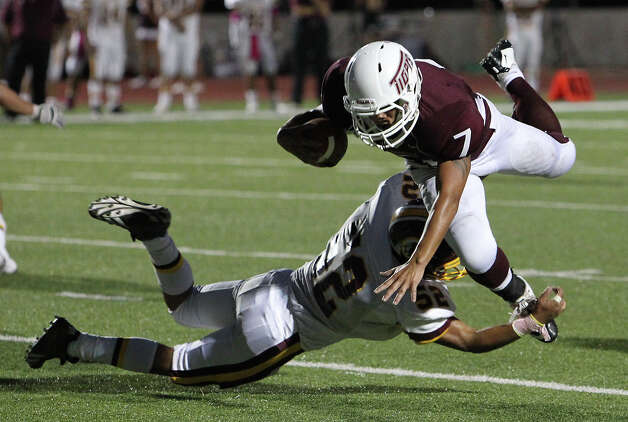 Floresville's Ruben Benavides (07) gets tripped up by Harlandale's Jonathan Rodriguez (32) in high school football in Floresville, Texas on Friday, Oct. 5, 2012. Photo: Kin Man Hui, Express-News / ©2012 San Antonio Express-News