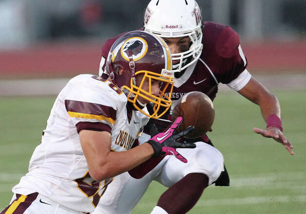 Harlandale's Nathan Ibarra (80) could not reel in a pass against Floresville's Gilbert Ortiz (01) in high school football in Floresville, Texas on Friday, Oct. 5, 2012. Photo: Kin Man Hui, Express-News / ©2012 San Antonio Express-News