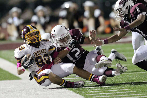 Harlandale's James Mendoza (88) gets shoved out of bounds by Floresville's Esteban Mireles (12) in high school football in Floresville, Texas on Friday, Oct. 5, 2012. Photo: Kin Man Hui, Express-News / ©2012 San Antonio Express-News