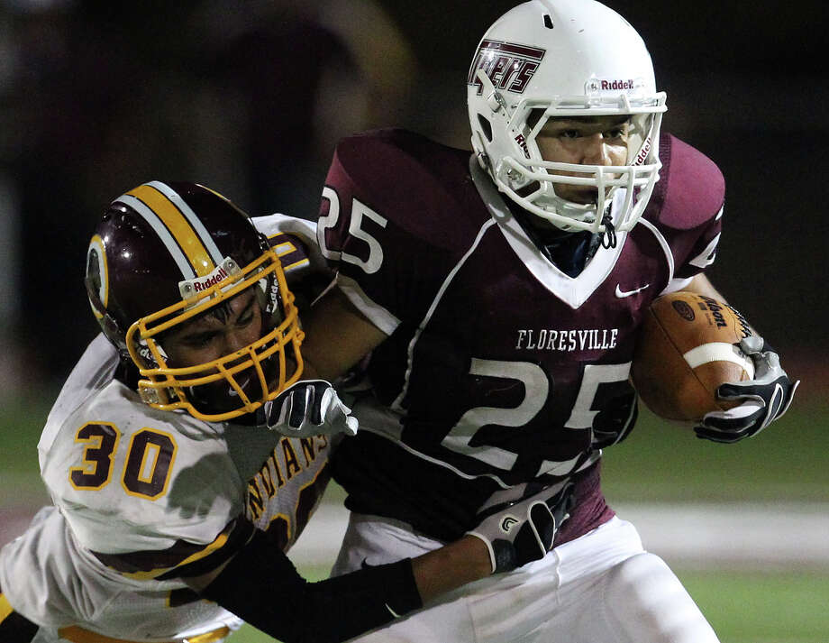 Floresville's Hector Villegas (25) tries to break away from Harlandale's Brandon Garza (30) in high school football in Floresville, Texas on Friday, Oct. 5, 2012. Photo: Kin Man Hui, Express-News / ©2012 San Antonio Express-News