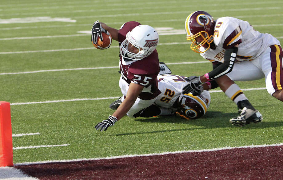 Floresville's Hector Villegas (25) attempts but just misses the goal line against Harlandale's Fabian Trevino (25) and Brandon Garza (30) in high school football in Floresville, Texas on Friday, Oct. 5, 2012. Photo: Kin Man Hui, Express-News / ©2012 San Antonio Express-News