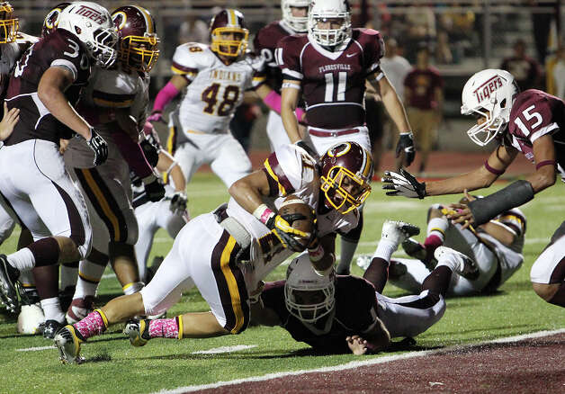 Harlandale's Nicholas Martinez (21) bulls in for a touchdown against Floresville's Gilbert Ortiz (01) in the first half in high school football in Floresville, Texas on Friday, Oct. 5, 2012. Photo: Kin Man Hui, Express-News / ©2012 San Antonio Express-News