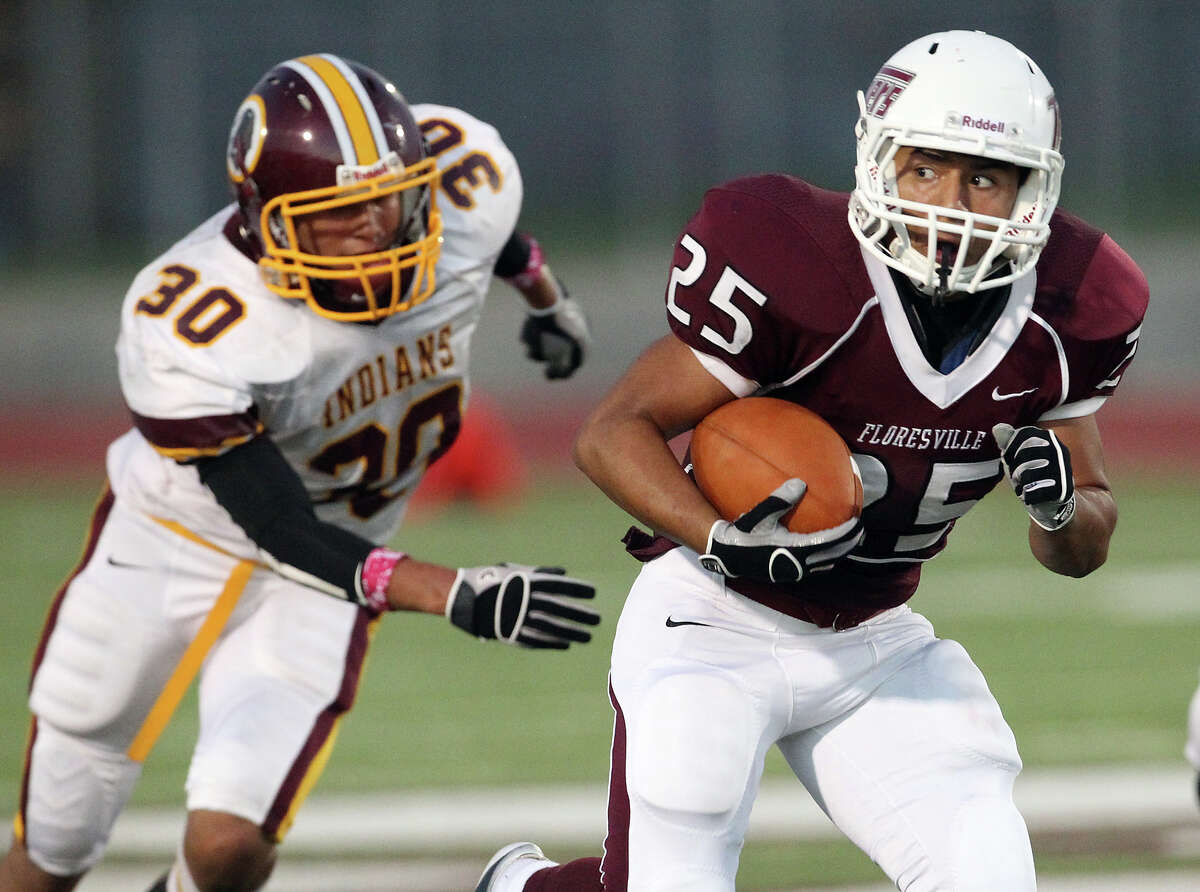 Floresville's Hector Villegas (25) takes a look back after slipping past Harlandale's Brandon Garza (30) in high school football in Floresville, Texas on Friday, Oct. 5, 2012.