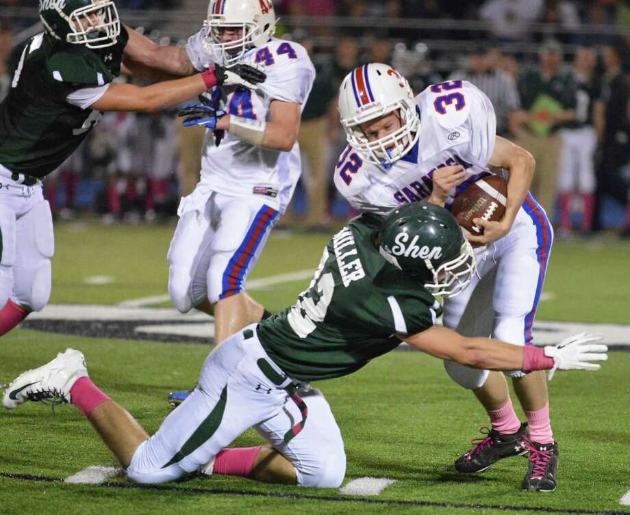 Shen's #32 Christopher Miller tackles Saratoga's #32 Nash Plowman during Friday night's game at Shenendehowa Oct. 5, 2012.  (John Carl D'Annibale / Times Union) Photo: John Carl D'Annibale / 00019493A