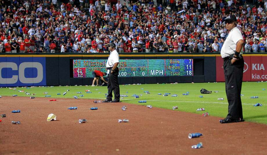 Atlanta Braves officials pick up trash on the field as security stand by during the eighth inning of the National League wild card playoff baseball game against the St. Louis Cardinals, Friday, Oct. 5, 2012, in Atlanta. The Cardinals won baseball's first wild-card playoff, taking advantage of a disputed infield fly call that led to a protest and fans littering the field with debris to defeat the Braves 6-3. (AP Photo/Todd Kirkland) Photo: Todd Kirkland