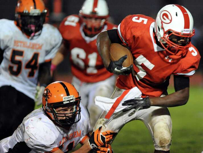 Guilderland's Micaiah Henningham (5), right, fights fro more yards during their football game agains