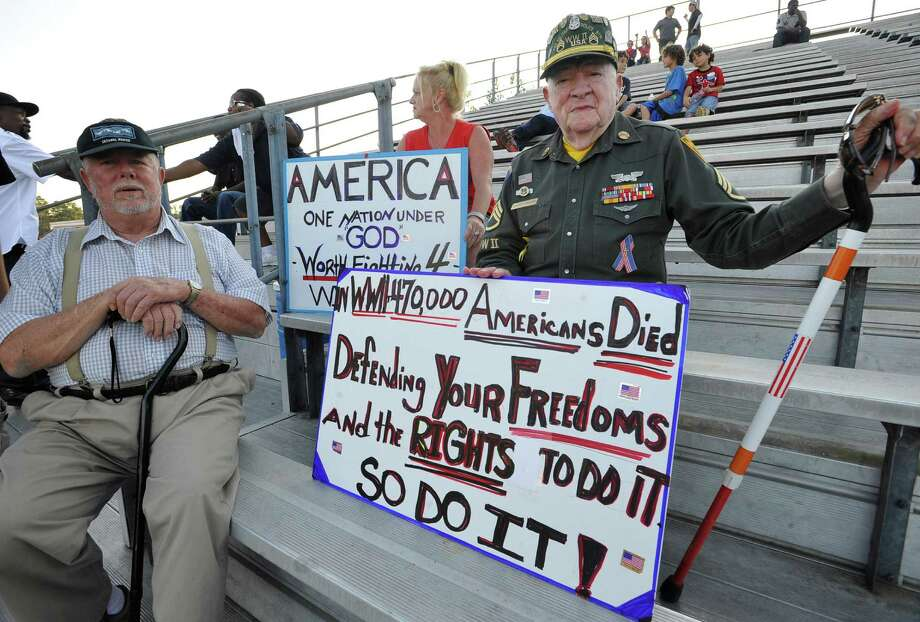 Charlie Henson, 89, right, his friend Jack Sammons, left, and Mitzi Toups, middle, show their support for the cheerleaders. This was the first home football game in Kountze since the sign controversy started and since the Thursday hearing that determined the cheerleaders could or could not use their faith-based signs.  Dave Ryan/The Enterprise Photo: Dave Ryan