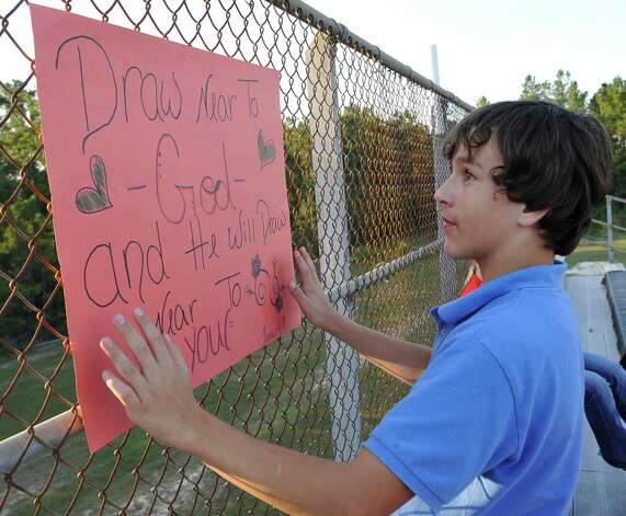 Jeremiah Barker, hangs a sign on the fence. This was the first home football game in Kountze since the sign controversy started and since the Thursday hearing that determined the cheerleaders could or could not use their faith-based signs.  Dave Ryan/The Enterprise Photo: Dave Ryan