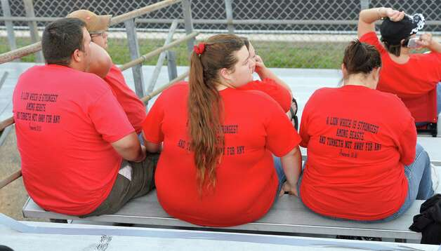 Zack Arrington, left, his fiancée Michelle Miller, middle, and Regina Miller, right, wear their shirts in support of the cheerleaders. This was the first home football game in Kountze since the sign controversy started and since the Thursday hearing that determined the cheerleaders could or could not use their faith-based signs.  Dave Ryan/The Enterprise Photo: Dave Ryan