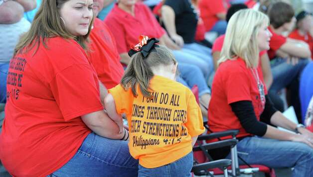 Little Cameryn Coplen, 4, shows her support next to her mother, Carol Coplen, left, in the stands before the start of the game. This was the first home football game in Kountze since the sign controversy started and since the Thursday hearing that determined the cheerleaders could or could not use their faith-based signs.  Dave Ryan/The Enterprise Photo: Dave Ryan
