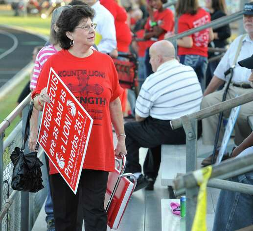 Ann Lawrence carries her son into the stands. Her granddaughter is a cheerleader. This was the first home football game in Kountze since the sign controversy started and since the Thursday hearing that determined the cheerleaders could or could not use their faith-based signs.  Dave Ryan/The Enterprise Photo: Dave Ryan