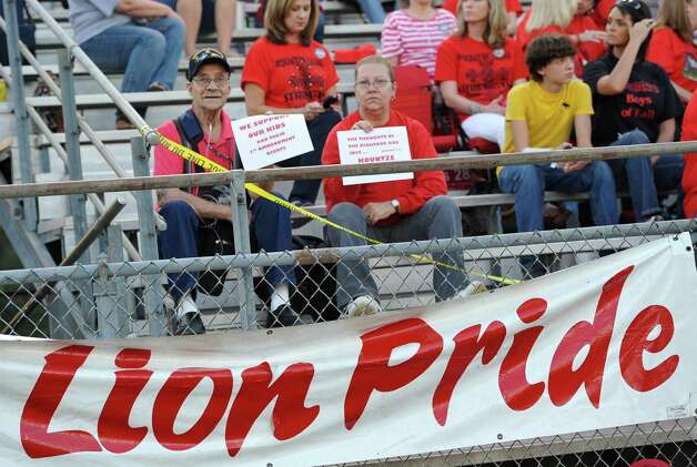 Chuck Coy, left, and Theresa Breaux, right, show their support at the start of the game. This was the first home football game in Kountze since the sign controversy started and since the Thursday hearing that determined the cheerleaders could or could not use their faith-based signs.  Dave Ryan/The Enterprise Photo: Dave Ryan