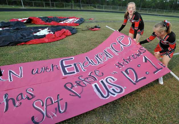 Morgan Coplen, left, and Ashton Jennings, right, ready the sign the team will run through.  This was the first home football game in Kountze since the sign controversy started and since the Thursday hearing that determined the cheerleaders could or could not use their faith-based signs.  Dave Ryan/The Enterprise Photo: Dave Ryan