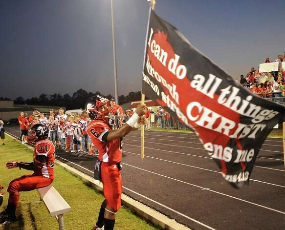 Kountze football player #6 Jamazdon Powell carries a flag as the team comes into the stadium.  This was the first home football game in Kountze since the sign controversy started and since the Thursday hearing that determined the cheerleaders could or could not use their faith-based signs.  Dave Ryan/The Enterprise Photo: Dave Ryan