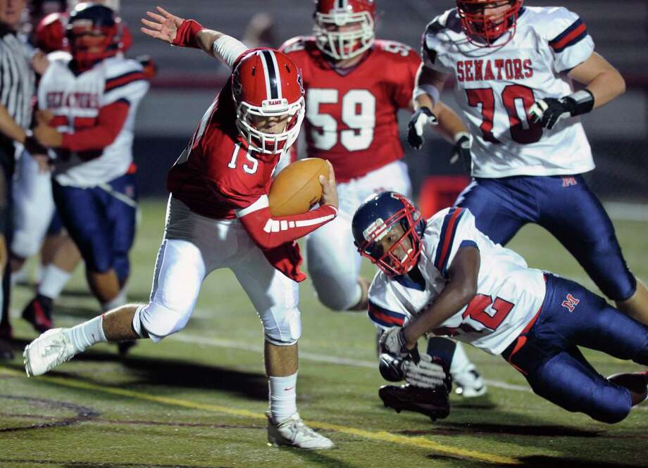 New Canaan's Nick Cascione evades a tackle as he runs for a touchdown during Friday's game against Brien McMahon High School at New Canaan on October 5, 2012. Photo: Lindsay Niegelberg / Stamford Advocate