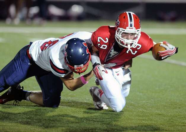 New Canaan's Alex LaPolice is tackled during Friday's game against Brien McMahon High School at New Canaan on October 5, 2012. Photo: Lindsay Niegelberg / Stamford Advocate