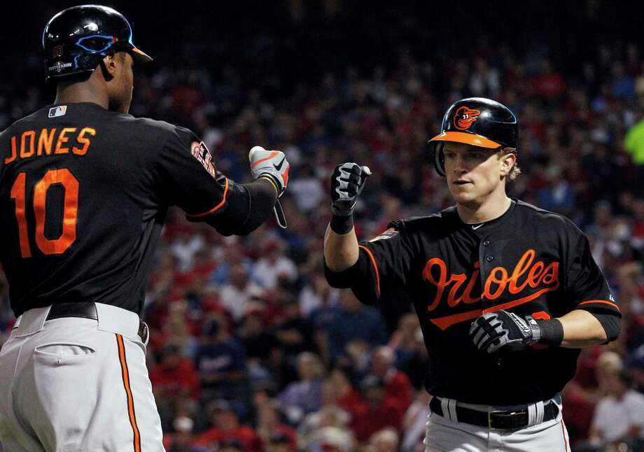 After scoring on a single by Baltimore Orioles' J.J. Hardy, Nate McLouth (9) celebrates with Adam Jones (10) during the first inning against the Texas Rangers in an American League wild-card playoff baseball game Friday, Oct. 5, 2012, in Arlington, Texas. (AP Photo/LM Otero) Photo: LM Otero