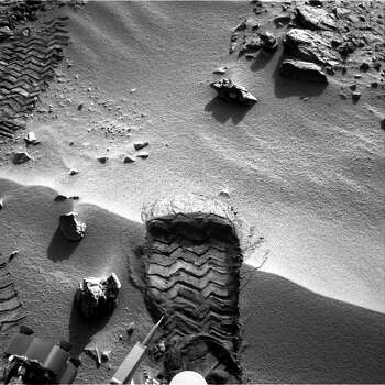 "This image released by NASA on October 4, 2012, shows  NASA's Mars rover Curiosity as it cut a wheel scuff mark into a wind-formed ripple at the ""Rocknest"" site to give researchers a better opportunity to examine the particle-size distribution of the material forming the ripple. The rover's right Navigation camera took this image of the scuff mark on the mission's 57th Martian day, or sol (October 3, 2012), the same sol that a wheel created the mark. For scale, the width of the wheel track is about 16 inches (40 centimeters). Photo: AFP PHOTO / NASA / JPL-Caltech / AFP"