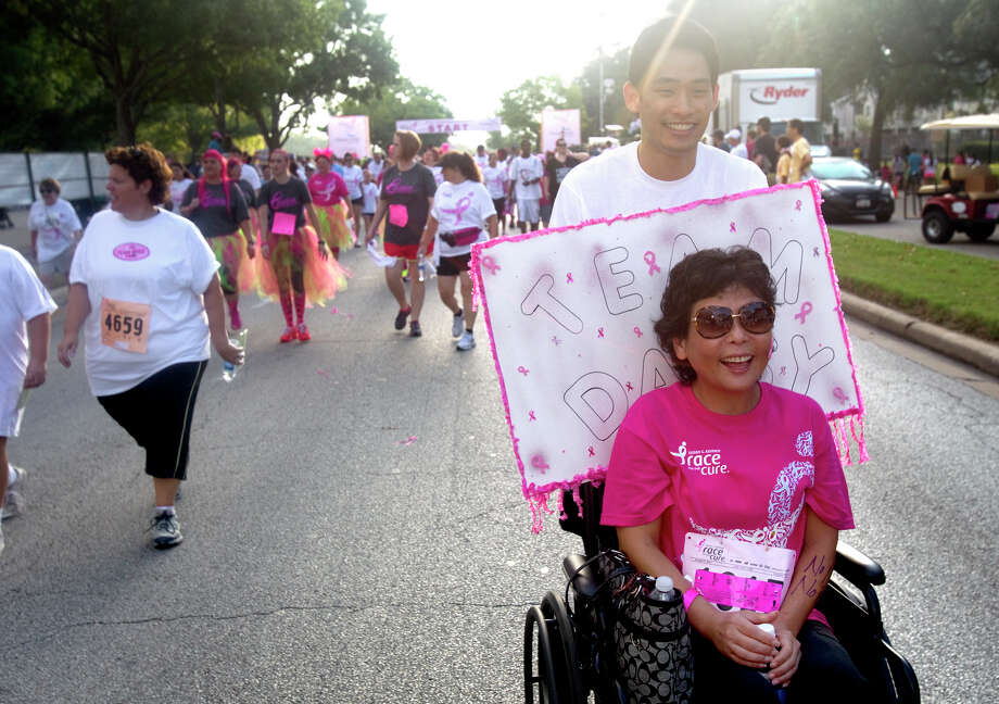 Eugene Kim pushes his aunt, Daisy Diaz during the Komen Race for the Cure on Allen Parkway Saturday, Oct. 6, 2012, in Houston. The race is to raise awareness for breast cancer as well as celebrate breast cancer survivors. Over 20,000 people attended the race. Photo: Cody Duty, Houston Chronicle / © 2012 Houston Chronicle