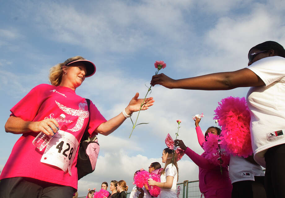 Four-year-survivor Terri Clark, left, receives a pink carnation from Briahn Hawkins, right, upon finishing the Komen Race for the Cure on Allen Parkway Saturday, Oct. 6, 2012, in Houston. The race is to raise awareness for breast cancer as well as celebrate breast cancer survivors. Over 20,000 people attended the race. Photo: Cody Duty, Houston Chronicle / © 2012 Houston Chronicle