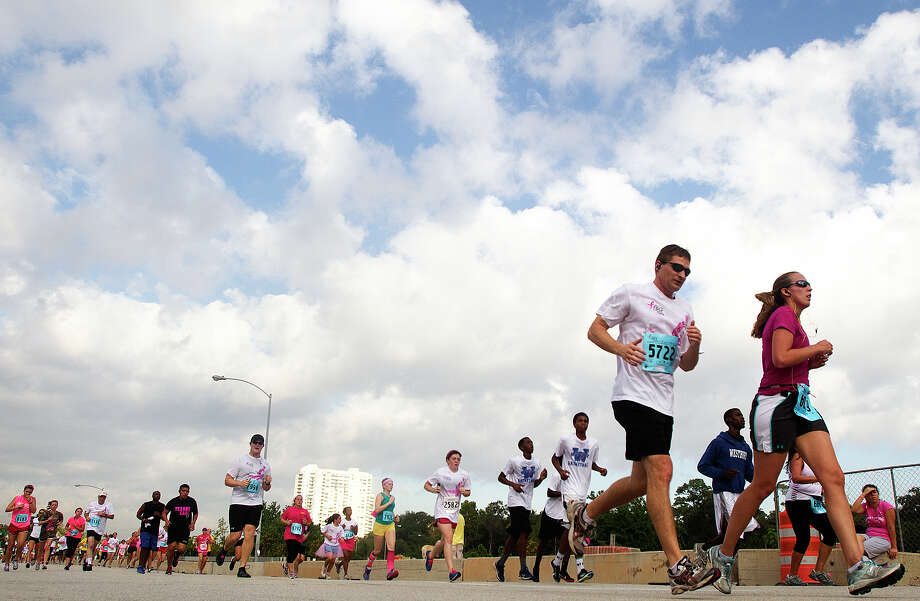 Runners compete in the Komen Race for the Cure on Allen Parkway Saturday, Oct. 6, 2012, in Houston. The race is to raise awareness for breast cancer as well as celebrate breast cancer survivors. Over 20,000 people attended the race. Photo: Cody Duty, Houston Chronicle / © 2012 Houston Chronicle